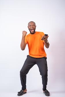 Opgewonden jonge nigeriaanse man viert feest terwijl hij naar zijn telefoon kijkt die op een witte muur is geïsoleerd