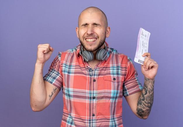 Opgewonden jonge reiziger man met koptelefoon om zijn nek die een vliegticket vasthoudt en de vuist omhoog houdt geïsoleerd op een paarse muur met kopieerruimte