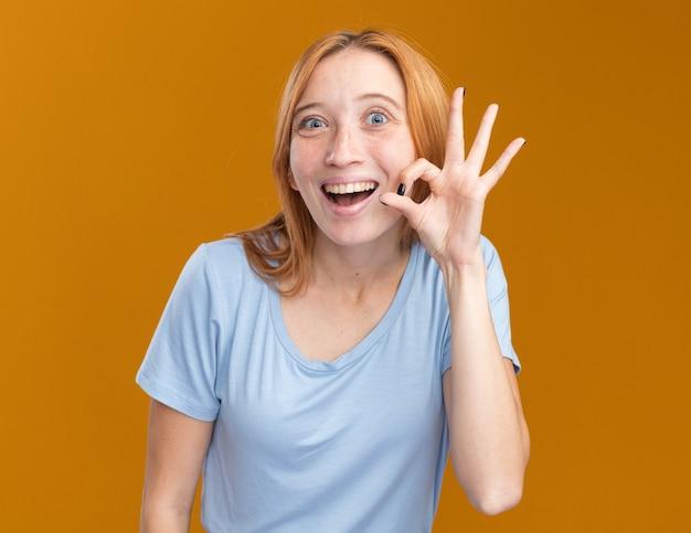 Opgewonden jonge roodharige gember meisje met sproeten gebaren ok teken geïsoleerd op oranje muur met kopie ruimte