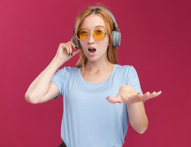 Opgewonden jonge roodharige gember meisje met sproeten in zonnebril en op koptelefoon houdt hand open geïsoleerd op roze muur met kopieerruimte