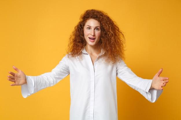Opgewonden jonge roodharige vrouw meisje in wit overhemd poseren geïsoleerd op geel oranje muur