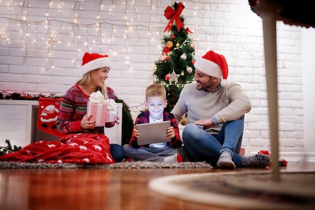 Opgewonden jonge schattige ouders brengen een geweldige tijd door met hun gelukkige kind terwijl ze op een tapijt zitten met cadeautjes en een tablet in het warme huis voor de kerstvakantie.