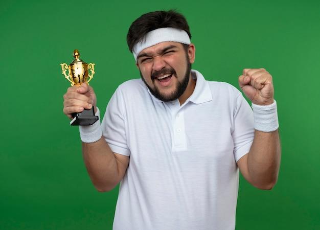 Opgewonden jonge sportieve man met hoofdband en polsbandje houden winnaar beker weergegeven: ja gebaar geïsoleerd op groen