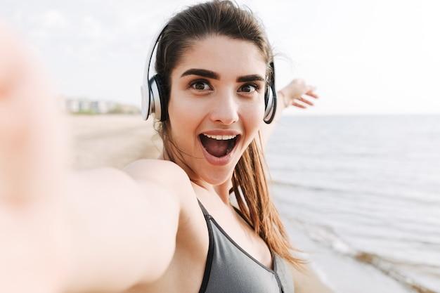 Opgewonden jonge sportvrouw die met koptelefoon een selfie neemt