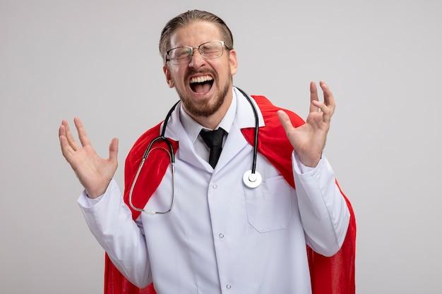Opgewonden jonge superheld man met gesloten ogen, het dragen van medische mantel met een stethoscoop en een bril geïsoleerd op een witte achtergrond