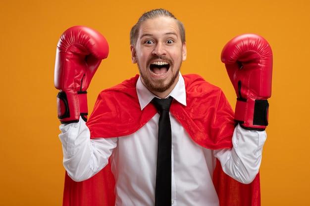 Opgewonden jonge superheld man met stropdas en bokshandschoenen verhogen handen geïsoleerd op oranje