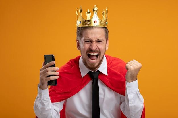 Opgewonden jonge superheld man met stropdas en kroon houden telefoon weergegeven: ja gebaar geïsoleerd op een oranje achtergrond