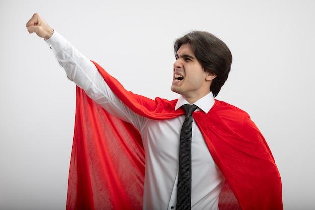 Opgewonden jonge superheld man stropdas dragen vuist omhoog geïsoleerd op een witte achtergrond