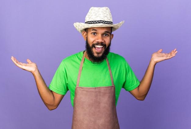 Opgewonden jonge tuinman afro-amerikaanse man met een tuinhoed die handen verspreidt die op een blauwe muur zijn geïsoleerd