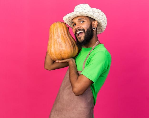 Opgewonden jonge tuinman afro-amerikaanse man met een tuinhoed met pompoen