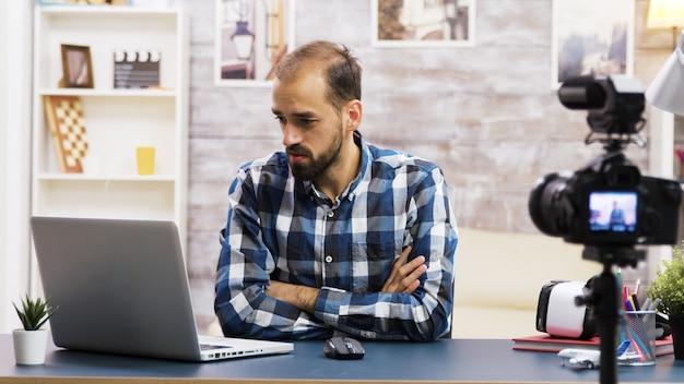 Opgewonden jonge vlogger tijdens een gesprek met abonnees na het lezen van goed nieuws op laptop. creatieve contentmaker.