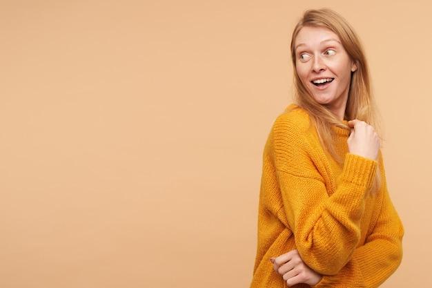 Opgewonden jonge vrij langharige roodharige dame die verrast haar wenkbrauwen opheft terwijl ze op haar schouder kijkt, staande op beige in vrijetijdskleding
