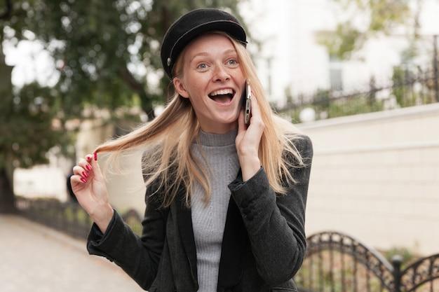 Opgewonden jonge vrolijke mooie blonde vrouw trekt aan haar haar met opgeheven hand en kijkt vooruit met grote ogen en mond geopend terwijl ze een levendig gesprek aan de telefoon heeft