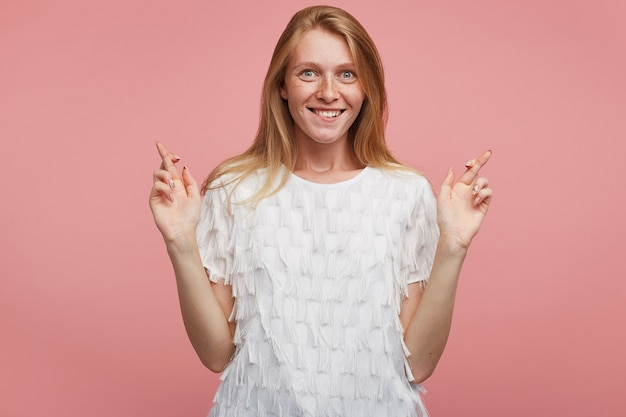 Opgewonden jonge vrolijke roodharige vrouw met natuurlijke make-up handen met gekruiste vingers opheffen en opgewonden kijken naar camera met brede vrolijke glimlach, staande op roze achtergrond
