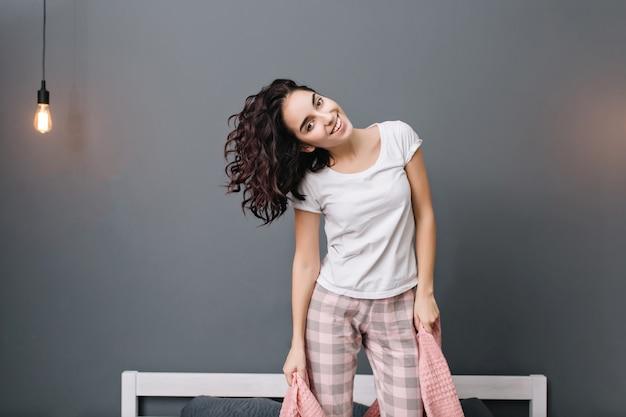 Opgewonden jonge vrolijke vrouw met donkerbruin krullend haar in pyjama's met plezier op bed. glimlachen, echte positieve emoties uiten, thuis chillen in een modern appartement