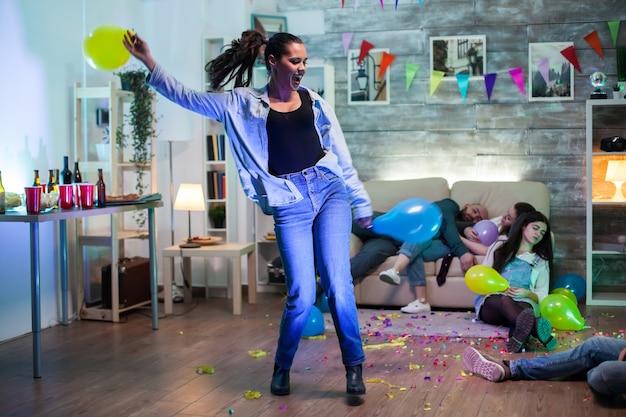 Opgewonden jonge vrouw dansen op een feestje. mensen die op de grond slapen.