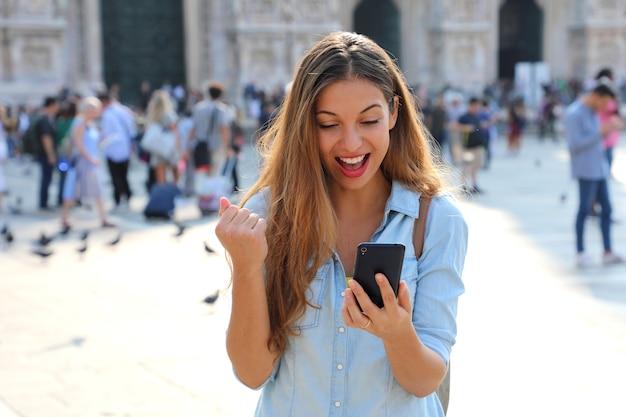 Opgewonden jonge vrouw die goed nieuws online ontvangt in een slimme telefoon buiten op straat