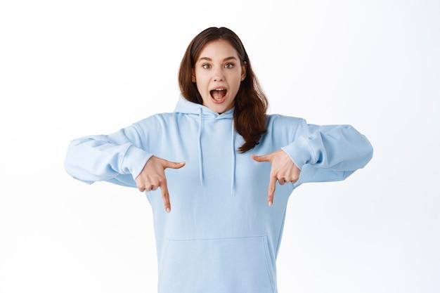 Opgewonden jonge vrouw die met de vingers naar beneden wijst en van vreugde schreeuwt, geweldige promo-deal laat zien, advertentie op kopieerruimte demonstreert, over witte muur staat