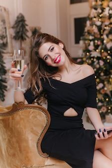 Opgewonden jonge vrouw die met trendy make-up wijnglas met glimlach opheft. blij europees meisje draagt een zwarte jurk en viert kerst thuis.