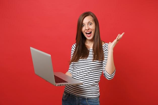 Opgewonden jonge vrouw die mond wijd open houdt, verbaasd kijkt, handen spreidt die op een laptop pc-computer werken die op rode achtergrond wordt geïsoleerd. mensen oprechte emoties levensstijl concept. bespotten kopie ruimte.
