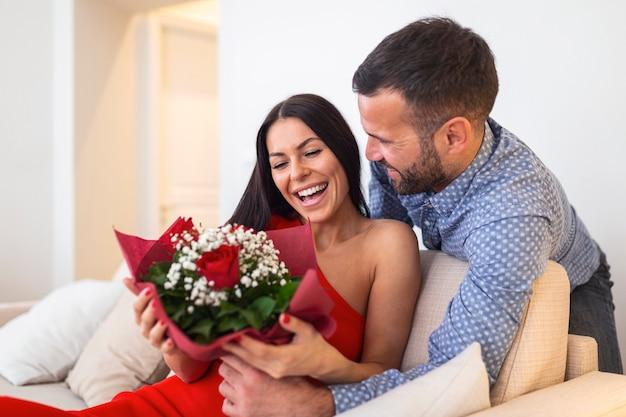 Opgewonden jonge vrouw die onverwacht boeket van rode rozen van echtgenoot ontvangt