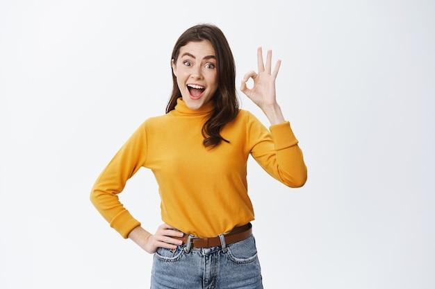 Opgewonden jonge vrouw die reclame maakt voor een goed product, een ok-teken toont en ja zegt, iets cools goedkeurt, een geweldige keuze prijst, blij staat tegen een witte muur