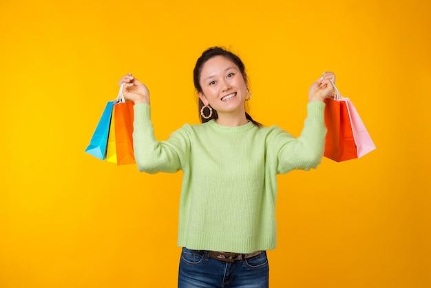 Opgewonden jonge vrouw houdt een aantal boodschappentassen