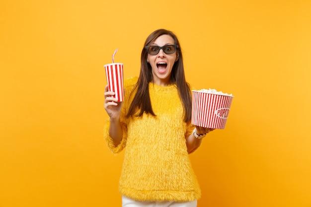 Opgewonden jonge vrouw in 3d imax bril kijken naar film film met emmer popcorn, plastic beker cola of frisdrank geïsoleerd op gele achtergrond. mensen oprechte emoties in de bioscoop, lifestyle concept.