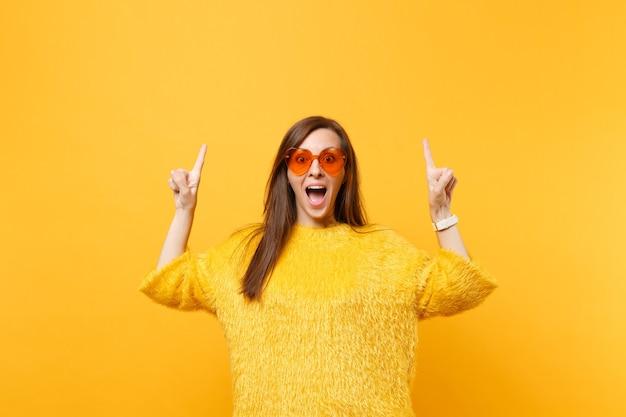 Opgewonden jonge vrouw in bont trui en hart oranje bril wijzende wijsvingers omhoog op kopie ruimte geïsoleerd op heldere gele achtergrond. mensen oprechte emoties, lifestyle concept. reclame gebied.