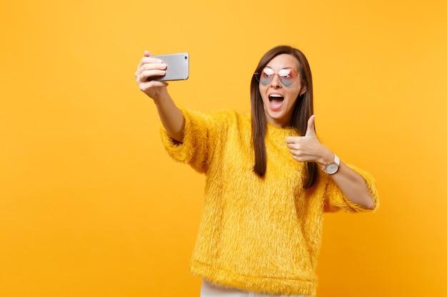 Opgewonden jonge vrouw in bont trui, hart bril duim opdagen, doen selfie schot op mobiele telefoon geïsoleerd op felgele achtergrond. mensen oprechte emoties, levensstijl. reclame gebied.