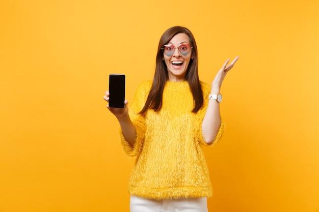 Opgewonden jonge vrouw in een hartbril die handen spreidt en mobiele telefoon vasthoudt met een leeg zwart leeg scherm geïsoleerd op een felgele achtergrond. mensen oprechte emoties, levensstijl. reclame gebied.