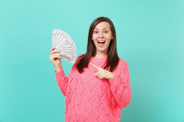 Opgewonden jonge vrouw in gebreide roze trui wijzende wijsvinger op veel bos dollars bankbiljetten, contant geld in de hand geïsoleerd op blauwe muur achtergrond. mensen levensstijl concept. bespotten kopie ruimte.