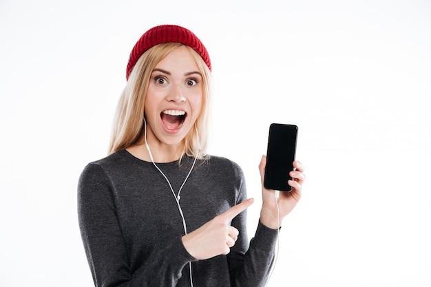 Opgewonden jonge vrouw in hoed wijzende vinger op leeg scherm mobiele telefoon