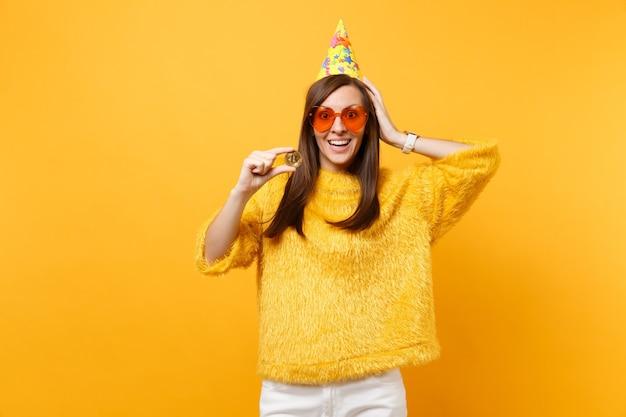 Opgewonden jonge vrouw in oranje hart bril, verjaardag hoed hand op het hoofd houden bitcoin metalen munt van gouden kleur toekomstige valuta geïsoleerd op gele achtergrond. mensen oprechte emoties levensstijl.