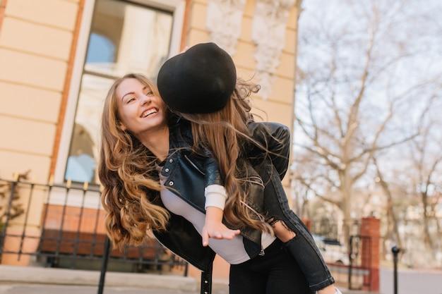 Opgewonden jonge vrouw in stijlvolle outfit tijd buiten doorbrengen met haar langharige krullende dochter. portret van vrolijk meisje met zusje gek rond op de achtergrond van de stad in de ochtend.