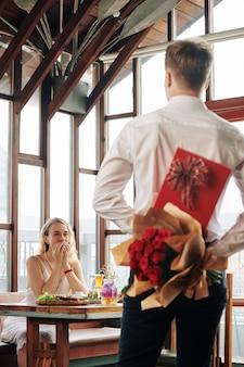 Opgewonden jonge vrouw kijken naar vriendje met doos chocolade en bloemen die naar haar tafel komen