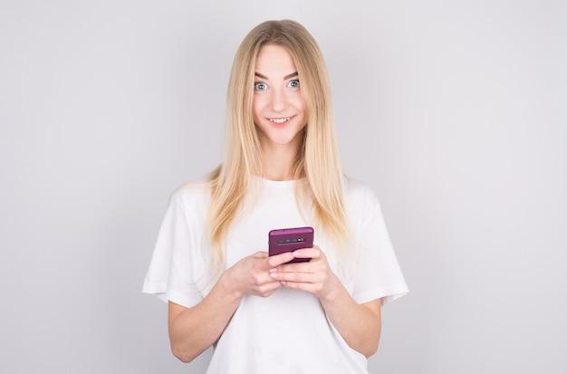 Opgewonden jonge vrouw kijkt verbaasd naar camera met mobiele telefoon, glimlachend. vrouw leest een tekstbericht op haar telefoon, geïsoleerd op een witte achtergrond.
