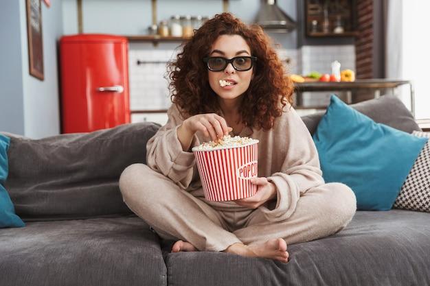 Opgewonden jonge vrouw met een 3d-bril die popcorn eet terwijl ze op de bank in het appartement zit