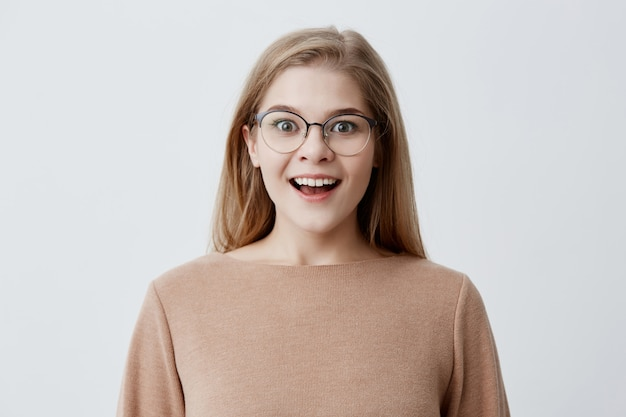Opgewonden jonge vrouw met een europees uiterlijk in een bruine losse trui, met blond haar, in een bril, breed glimlachend van verbazing en haar perfecte witte tanden laten zien. jeugd en geluk