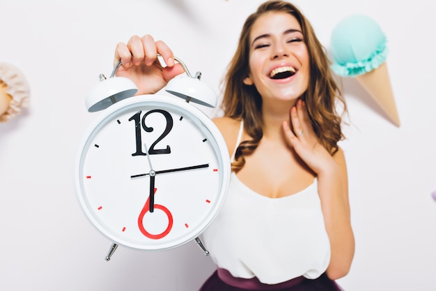 Opgewonden jonge vrouw met grote klok in de hand te wachten op verjaardagsfeestje begint staan op versierde muur. close-upportret van vrolijk meisje verheugt zich aan het eind van de werkdag.