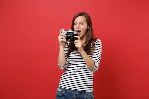 Opgewonden jonge vrouw met retro vintage fotocamera die haar mond wijd open houdt en er verbaasd uitziet