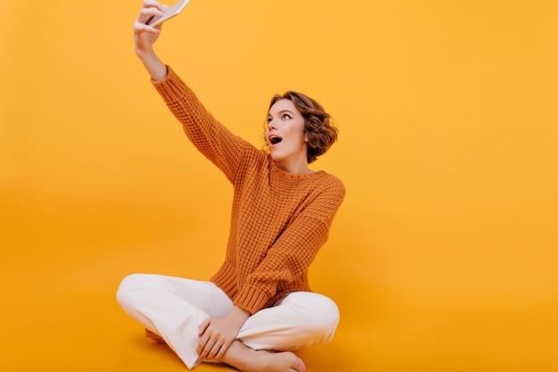 Opgewonden jonge vrouw met stijlvol kapsel selfie maken zittend met gekruiste benen