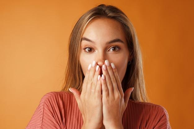 Opgewonden jonge vrouw mond sluiten met haar hand tegen oranje achtergrond
