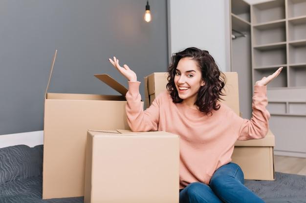 Opgewonden jonge vrouw op bed surround dozen, karton glimlachend in modern appartement. verhuizen naar een nieuw appartement, echte positieve emoties uiten in een nieuw huis met een modern interieur