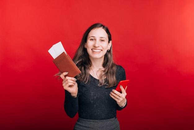 Opgewonden jonge vrouw toont haar paspoort en enkele kaartjes erin en houdt haar telefoon op rode ruimte.