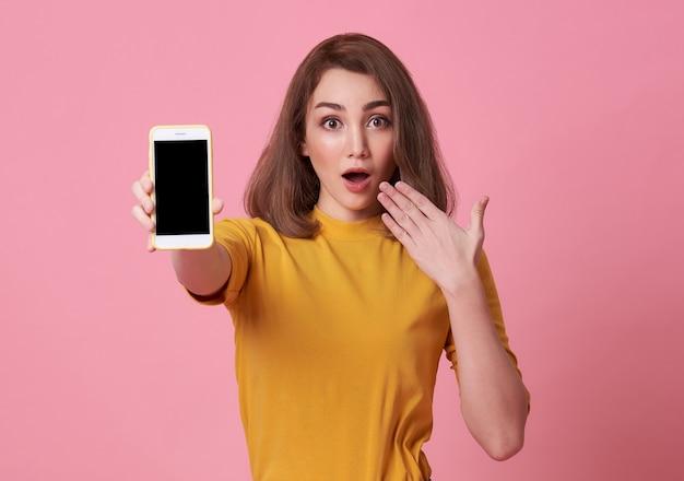Opgewonden jonge vrouw toont op leeg scherm mobiele telefoon geïsoleerd op roze achtergrond
