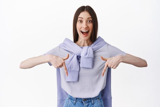 Opgewonden jonge vrouw vond een goede deal, wijzend op promotionele tekst met gefascineerd gezicht, hijgend en glimlachend gelukkig, met advertentiebalg, witte muur