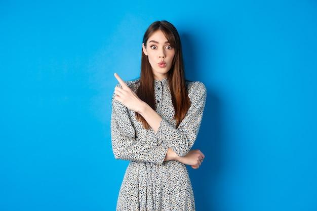 Opgewonden jonge vrouw zegt wauw, ziet er onder de indruk uit en wijst naar links naar logo, toont geweldig nieuws, staat schattige jurk op blauwe achtergrond