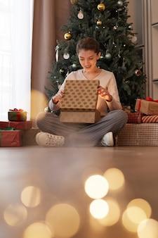 Opgewonden jonge vrouw zit met gekruiste benen in de buurt van een versierde boom en opent de doos van de kerstcadeau