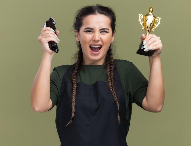 Opgewonden jonge vrouwelijke kapper in uniform met tondeuses met winnaar beker geïsoleerd op olijfgroene muur